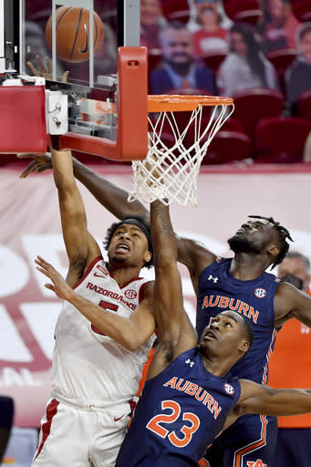 Arkansas guard Moses Moody (5) shoots as Auburn's Jaylin Williams (23) and Babatunde Akingbola defend during the first half of an NCAA college basketball game Wednesday, Jan. 20, 2021, in Fayetteville, Ark. (AP Photo/Michael Woods)
