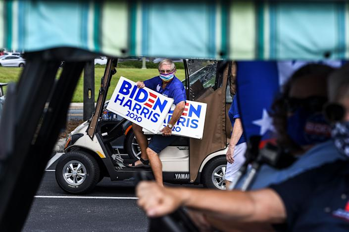 """A resident of The Villages, Florida, holds a """"Biden Harris 2020"""" campaign poster on August 21, 2020, as he participates in a golf cart parade to celebrate the nomination of Joe Biden for Democratic presidential candidate and Kamala Harris for vice president. (Chandan Khanna/AFP via Getty Images)"""