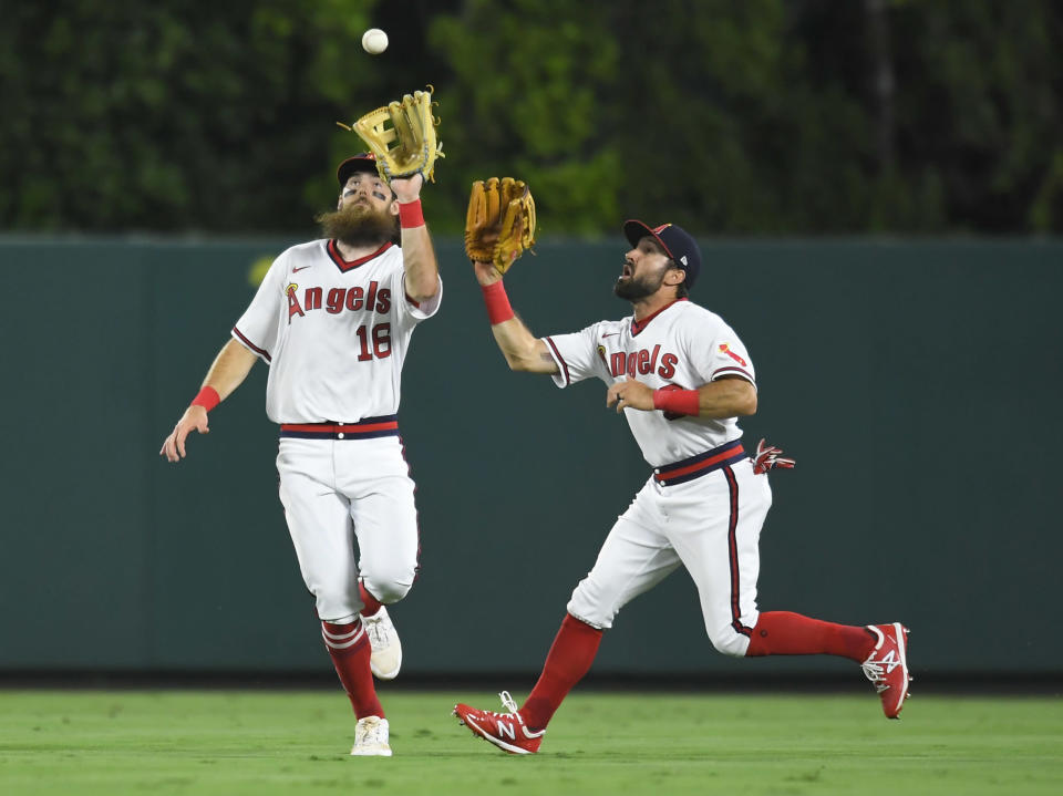 Los Angeles Angels center fielder Brandon Marsh, left, runs in front of right fielder Adam Eaton to catch a fly ball hit by Oakland Athletics' Jed Lowrie in the eighth inning of a baseball game against Friday, July 30, 2021, in Anaheim, Calif. (AP Photo/John McCoy)