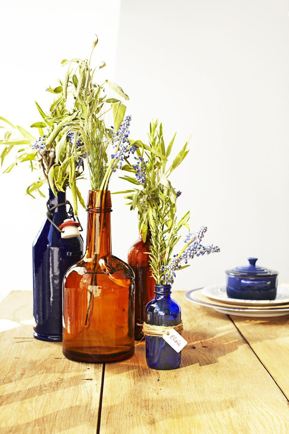 "<p>Scour your local flea market for blue and amber glass vessels. Fill some with flowers or herbs — leftover sage from the kitchen fits the theme — and use the smaller ones as place cards.</p><p><a class=""link rapid-noclick-resp"" href=""https://www.amazon.com/Couronne-Company-B6533T15-Apothecary-Recycled/dp/B06Y63M953?tag=syn-yahoo-20&ascsubtag=%5Bartid%7C10055.g.1681%5Bsrc%7Cyahoo-us"" rel=""nofollow noopener"" target=""_blank"" data-ylk=""slk:SHOP GLASS BOTTLES"">SHOP GLASS BOTTLES</a></p>"