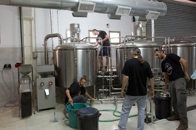 Israeli employees make gluten-free beer at the Meadan Brewing in the northern Israeli city of Karmiel (AFP Photo/Menahem Kahana)