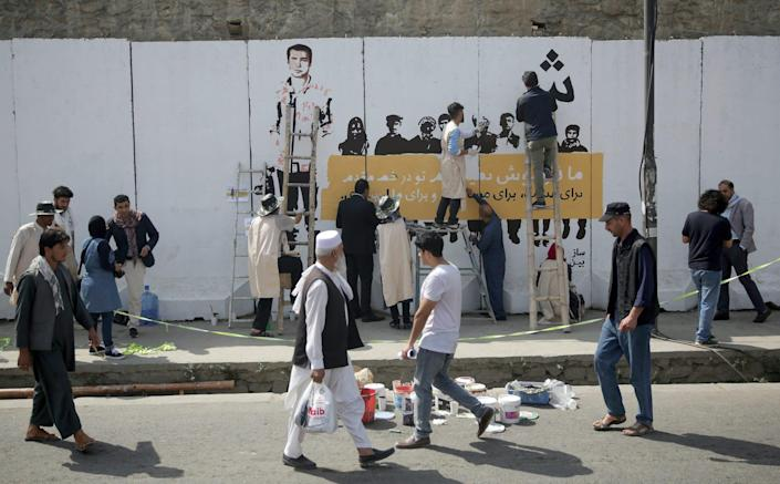 Artists paint a mural of killed journalists on a wall