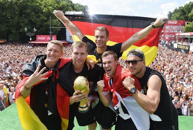 "German soccer players from left: Bastian Schweinsteiger, Per Mertesacker, goalie Manuel Neuer, Kevin Grosskreutz, and Lukas Podolski celebrate on stage at the German team victory ceremony , near the Brandenburg Gate in Berlin, Tuesday July 15, 2014. Germany's World Cup winners shared their fourth title with hundreds of thousands of fans by parading the trophy through cheering throngs to celebrate at the Brandenburg Gate on Tuesday. An estimated 400,000 people packed the ""fan mile"" in front of the Berlin landmark to welcome home coach Joachim Loew's team and the trophy which returned to Germany for the first time in 24 years. (AP Photo/ Markus Gilliar,Pool)"