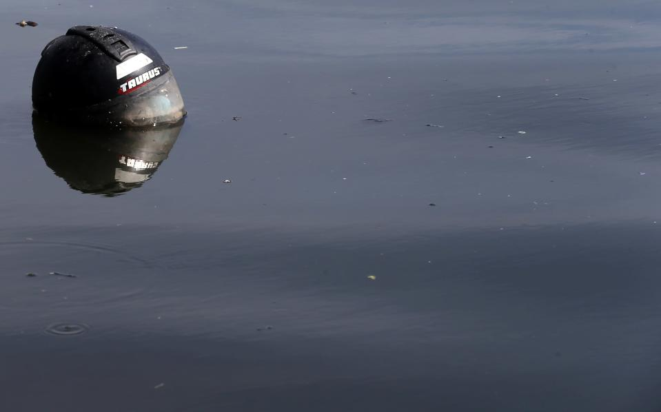 A helmet is seen at the Guanabara Bay in Rio de Janeiro March 12, 2014. According to the local media, the city of Rio de Janeiro continues to face criticism locally and abroad that the bodies of water it plans to use for competition in the 2016 Olympic Games are too polluted to host events. Untreated sewage and trash frequently find their way into the Atlantic waters of Copacabana Beach and Guanabara Bay - both future sites to events such as marathon swimming, sailing and triathlon events. Picture taken on March 12, 2014. REUTERS/Sergio Moraes (BRAZIL - Tags: ENVIRONMENT SPORT OLYMPICS)