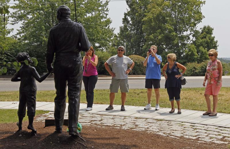 "FILE - This July 3, 2012 file photo shows people gathering around a statue of Andy and Opie Taylor, characters from ""The Andy Griffith Show,"" at the Andy Griffith Playhouse in Mount Airy, N.C., Tourism in Mount Airy is up since Andy Griffith died July 3, with about 10,400 people visiting the Andy Griffith Museum in July, almost double the 5,400 who visited in July 2011. (AP Photo/Gerry Broome)"