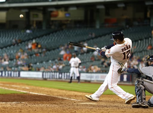 Houston Astros' Carlos Pena (12) hits a game-winning three-run home run during the 10th inning of an interleague baseball game against the Milwaukee Brewers Thursday, June 20, 2013, in Houston. The Astros won 7-4 in 10 innings. (AP Photo/David J. Phillip)