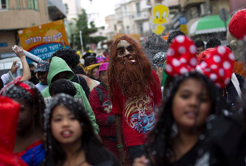 Young children of foreign migrant workers, wear masks as they march during a Purim parade in Tel Aviv, Israel, Friday, Feb. 22, 2013. (AP Photo/Ariel Schalit)
