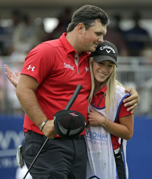 Patrick Reed, left, embraces his wife and caddie, Justine Reed, right, after making a birdie putt on the ninth hole during the second round of the Wyndham Championship golf tournament at Sedgefield Country Club in Greensboro, N.C., Friday, Aug. 16, 2013. (AP Photo/Chuck Burton)