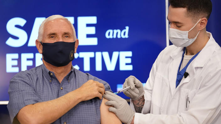 A health care working gives an injection into Mike Pence's left arm, both wear face masks.