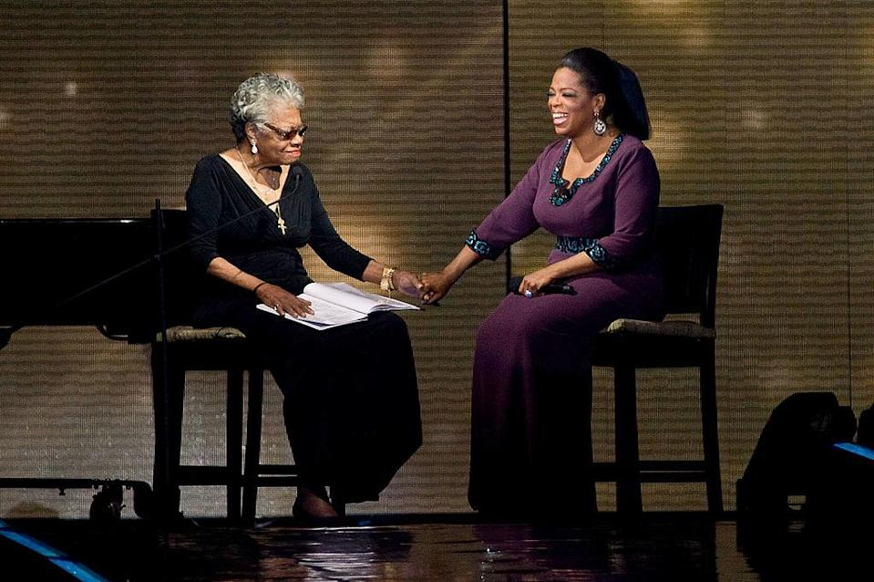 Maya Angelou and Oprah hold hands onstage
