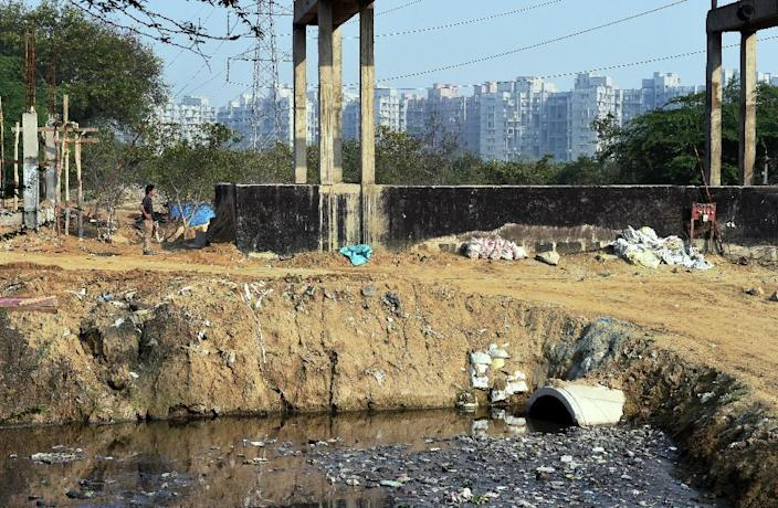 Construction can be seen near a drainage canal carrying refuse water from residential apartment buildings in the Dwarka sector of New Delhi, March 18, 2015 (AFP Photo/Roberto Schmidt)