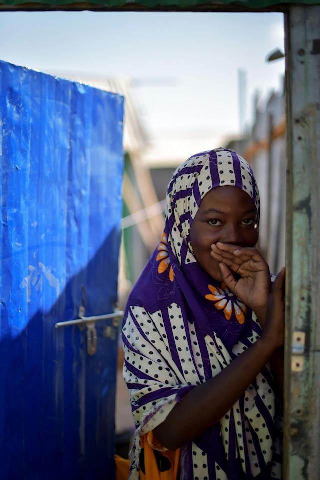 <p>A young Somali girl smiles while standing in the doorway to her home at the Dayniile Persons (IDP) camp in Mogadishu, Somalia, on March 6, 2017. (Photo: Tobin Jones/UN) </p>