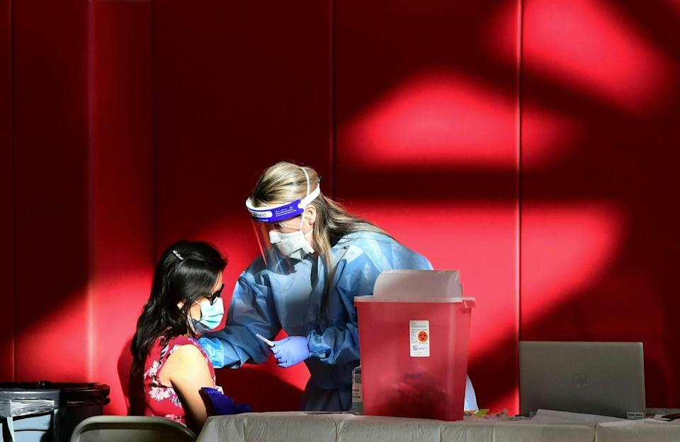 A registered nurse administers the COVID-19 vaccine to a woman.