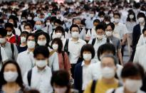 FILE PHOTO: People wearing protective masks amid the coronavirus disease (COVID-19) outbreak, make their way during rush hour at a railway station in Tokyo