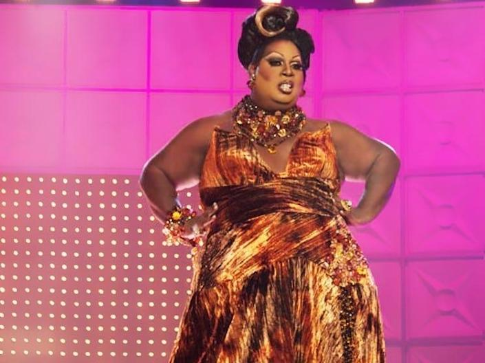 Latrice Royale in a gold gown with hair up on stage at drag race