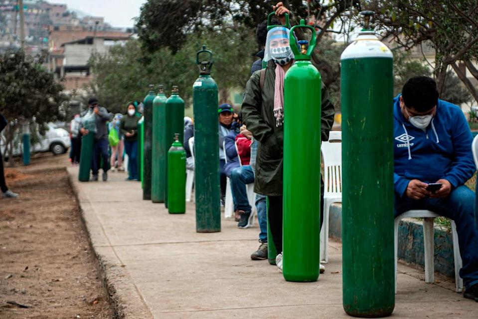 Relatives of COVID-19 patients queue to recharge oxygen cylinders. Source: AFP