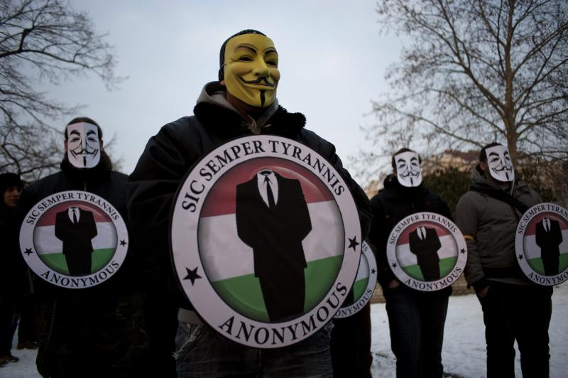 In this Saturday, Feb. 11, 2012, photo, protestors wearing Guy Fawks masks hold the logos of the international hacker group Anonymous during a demonstration against Anti-Counterfeiting Trade Agreement, ACTA, in Budapest, Hungary.  The shadowy world of Internet hackers and pranksters was rocked by news Tuesday, March 6, 2012, that Hector Xavier Monsegur, 28, one of the world's most-wanted and most-feared computer vandals has been an FBI informant for months and helped authorities build a case against five alleged comrades. (AP Photo/MTI, Janos Marjai)