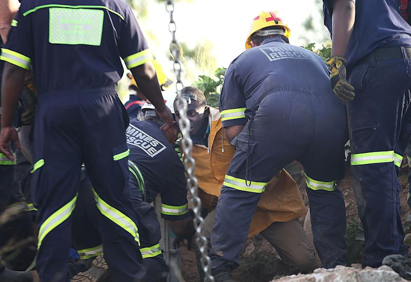 A trapped illegal miner is bought to the surface at a disused gold mine shaft near, Benoni, South Africa, Sunday, Feb. 16, 2014. Debris trapped a group of miners who were working illegally in an abandoned mine in South Africa, but rescue workers cleared the mine shaft entrance and at least 11 miners were escorted to safety Some of the miners still below the surface in the gold mine shaft near Johannesburg appeared to be reluctant to emerge because of fears they would be arrested (AP Photo) South Africa Out
