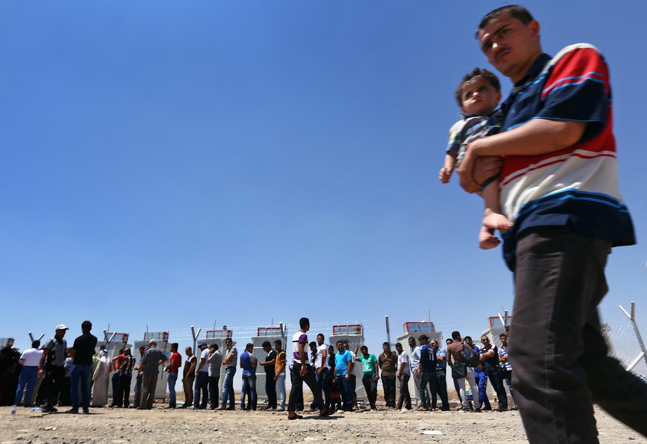 Iraqis who have fled the violence in their hometown of Mosul line up at Khazir refugee camp outside of Irbil, 217 miles (350 kilometers) north of Baghdad, Iraq, Monday, June 16, 2014. Sunni militants captured a strategic city along the highway to Syria on Monday, moving closer to their goal of linking areas under their control on both sides of the border. The al-Qaida breakaway group leading the push in Iraq also is fighting in the civil war next door in Syria where it controls territory abutting the Iraqi border.(AP Photo)