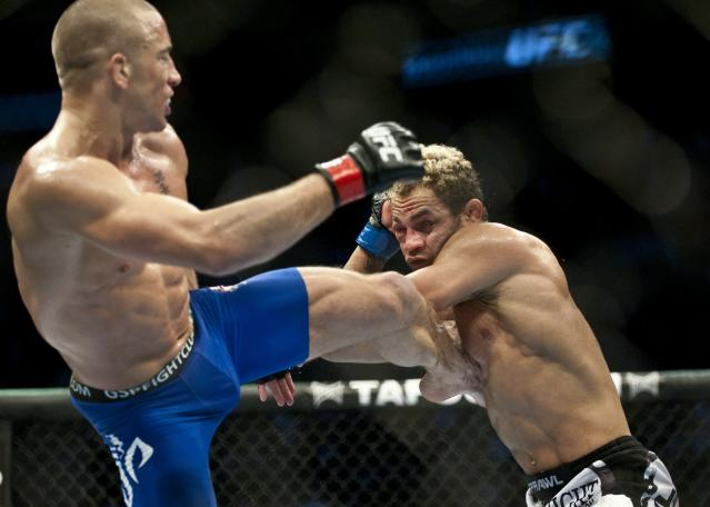 Georges St-Pierre (L) from Montreal, Canada kicks in the ribs of Josh Koscheck from Waynesburg US during the third round of the Ultimate Fighting Championship on December 11, 2010 at Bell Centre in Montreal, Quebec, Canada. AFP PHOTO / ROGERIO BARBOSA (Photo credit should read ROGERIO BARBOSA/AFP/Getty Images)