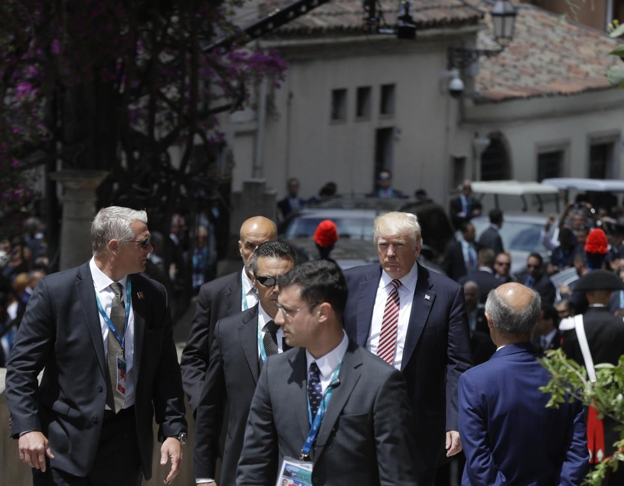 US President Donald Trump is surrounded by security guards as he arrives for a welcome ceremony for the G7 summit in the Ancient Theatre of Taormina (3rd century BC) in the Sicilian citadel of Taormina, Italy, Friday, May 26, 2017. On Friday and Saturday, for the first time all seven are around the same table, including also newcomers Emmanuel Macron of France, Theresa May of Britain and the Italian host, Paolo Gentiloni, forging a new dynamic after a year of global political turmoil amid a rise in nationalism. (AP Photo/Gregorio Borgia)