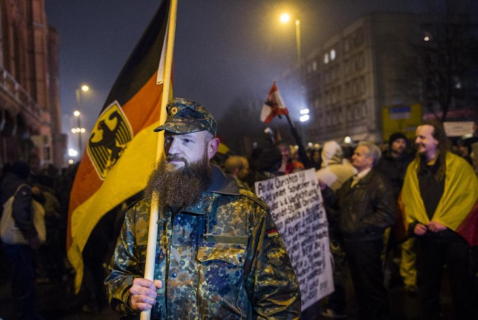 A man holds a German national flag during a rally by a mounting right-wing populist movement called Pegida, on January 5, 2015 in Berlin (AFP Photo/Odd Andersen )
