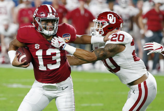 Alabama quarterback Tua Tagovailoa (13) fights off Oklahoma safety Robert Barnes (20), during the first half of the Orange Bowl NCAA college football game, Saturday, Dec. 29, 2018, in Miami Gardens, Fla. (AP Photo/Wilfredo Lee)