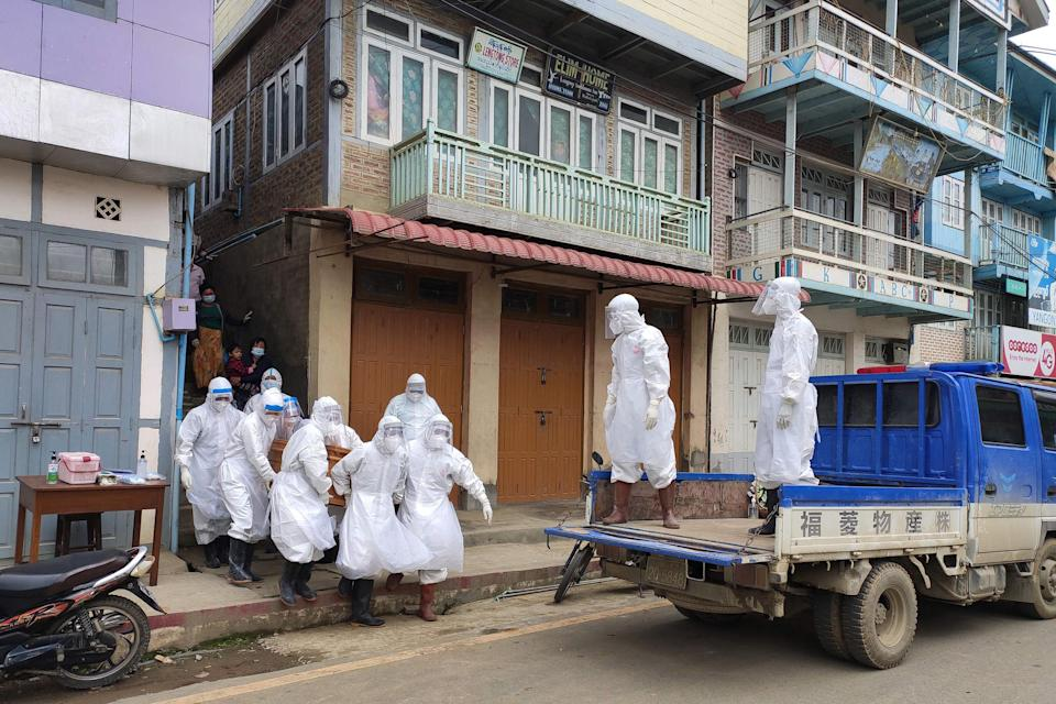 This handout photo from local media group Tedim Post taken and released on June 29, 2021, shows health workers carrying a coffin bearing the remains of a Covid-19 coronavirus victim who died at home in Tedim, western Chin state.
