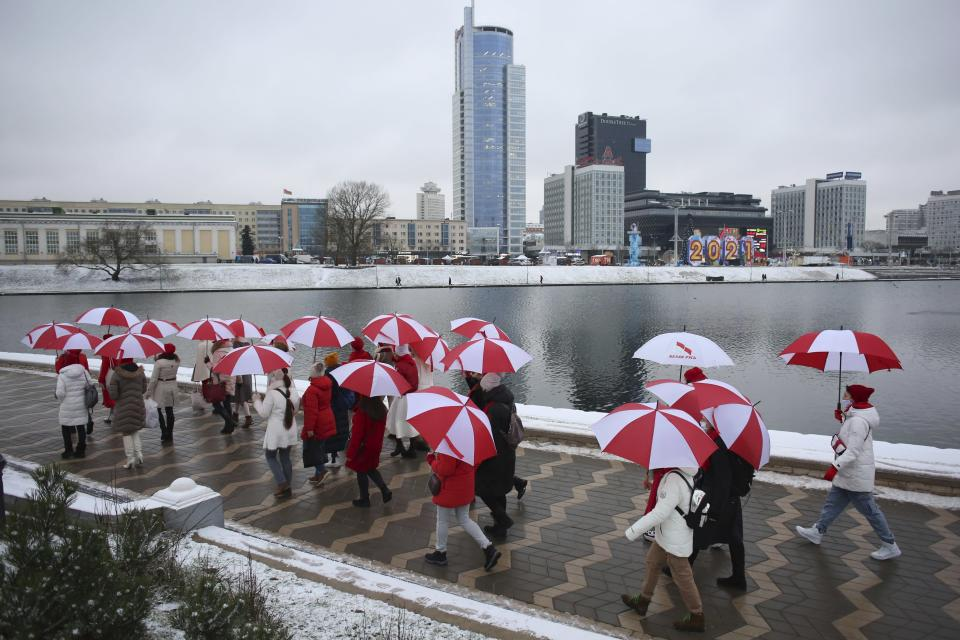 A group of people hold umbrellas in colors of old Belarusian national flag during an opposition action to protest the official presidential election results in Minsk, Belarus, Wednesday, Jan. 6, 2021. Winter's cold and harsh police have put a chill on the protests against President Alexander Lukashenko that gripped Belarus for months. But opposition forces are preparing to turn up the heat in the spring and observers say Lukashenko doesn't have a clear strategy to overcome new unrest. (AP Photo, File)
