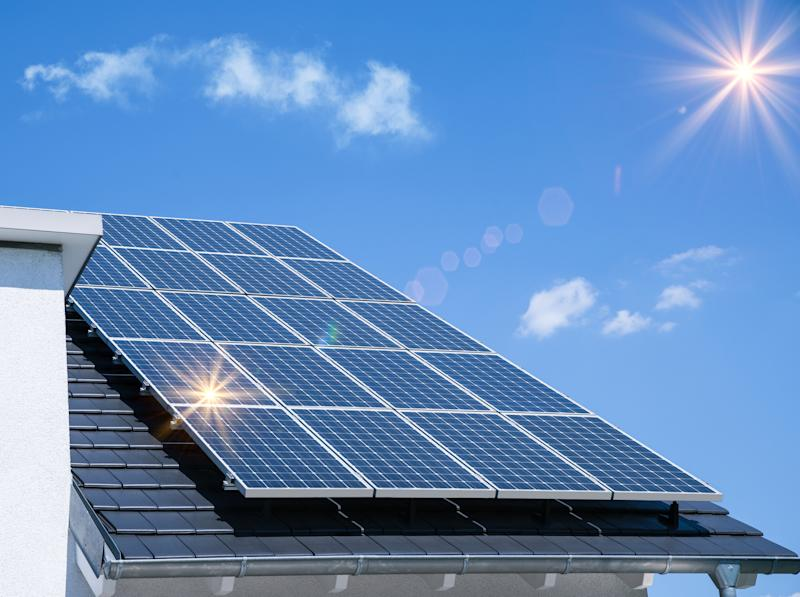 Set of solar panels on the roof of a house, with sun and sky above.