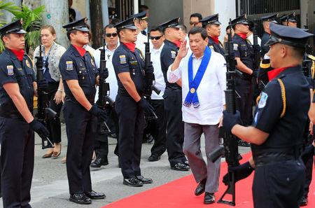 President Rodrigo Duterte salutes while passing members of custom police, upon arrival to witness the destruction of condemned smuggled luxury cars worth 61,626,000.00 pesos (approximately US$1.2 million), which include used Lexus, BMW, Mercedes-Benz, Audi, Jaguar and Corvette Stingray, during the 116th Bureau of Customs founding anniversary in Metro Manila, Philippines February 6, 2018. REUTERS/Romeo Ranoco