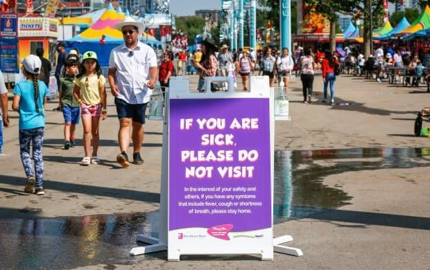 A COVID precaution sign at the Calgary Stampede on July 9, 2021. The Stampede is offering free admission for the final day of the festival, on Sunday, July 18. (Jeff McIntosh/Canadian Press - image credit)
