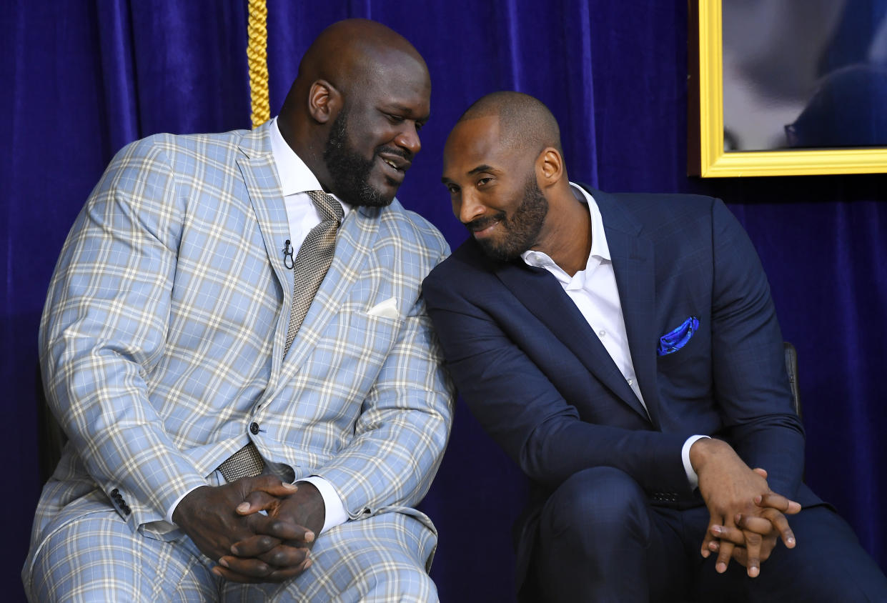 """In this March 24, 2017, file photo, Shaquille O'Neal, left, and Kobe Bryant chat at the unveiling of a statue of O'Neal in front of the Staples Center in Los Angeles. Bryant downplayed talk of a reignited feud with Shaquille O'Neal, saying there is """"nothing new"""" that has been said recently between the former teammates. Bryant had recently said that if O'Neal had worked harder, they could have won 12 rings together with the Los Angeles Lakers. O'Neal fired back on social media that they could have won more if Bryant had passed him the ball more often. But Bryant said Thursday, Aug. 29, 2019, during a visit to the U.S. Open tennis tournament that the comments don't mean they are fighting again. (AP Photo/Mark J. Terrill, File)"""