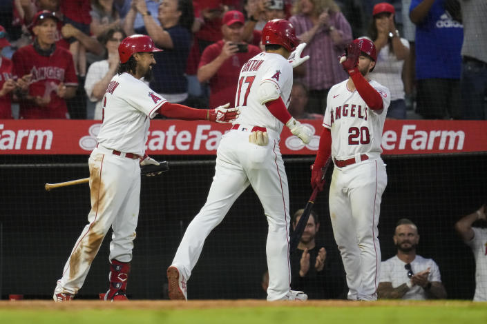 Los Angeles Angels designated hitter Shohei Ohtani (17) celebrates with Anthony Rendon, left, and Jared Walsh (20) after hitting a home run during the fourth inning of a baseball game against the Baltimore Orioles Friday, July 2, 2021, in Anaheim. David Fletcher also scored. (AP Photo/Ashley Landis)