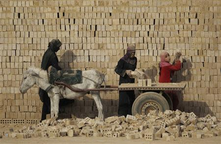 Female workers load bricks on a donkey-driven cart at a brick factory in the town of Nahrawan, east of Baghdad, in this March 8, 2012 file photo. REUTERS/Thaier al-Sudani/Files
