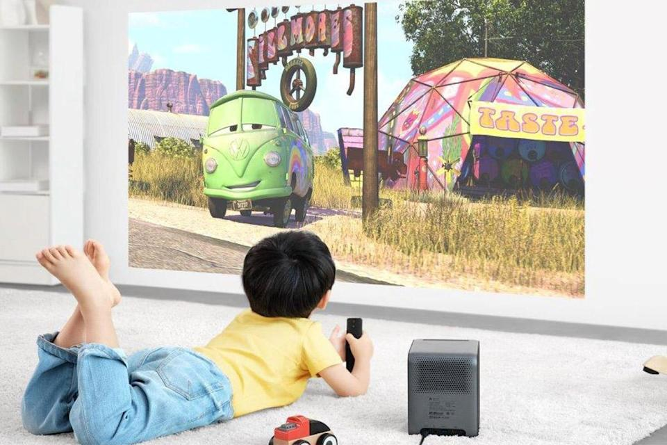a little boy in a yellow shirt and jeans lays on a carpet watching a Cars movie that is projected on the wall