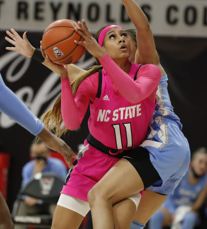 N.C. State's Jakia Brown-Turner (11) shoots as North Carolina's Stephanie Watts (5) defends during the first half of a college basketball game in the annual Play4Kay game at Reynolds Coliseum in Raleigh, N.C., Sunday, Feb. 21, 2021. (Ethan Hyman/The News & Observer via AP)
