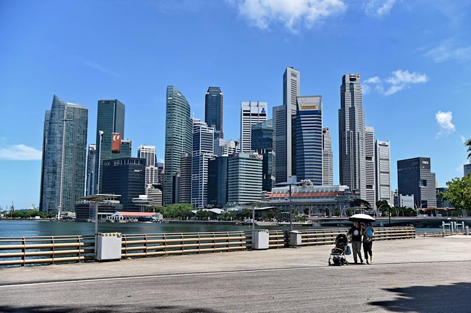 This photograph taken on May 6, 2019, shows people walking near the central business district in Singapore. (Photo by Roslan RAHMAN / AFP)        (Photo credit should read ROSLAN RAHMAN/AFP/Getty Images)