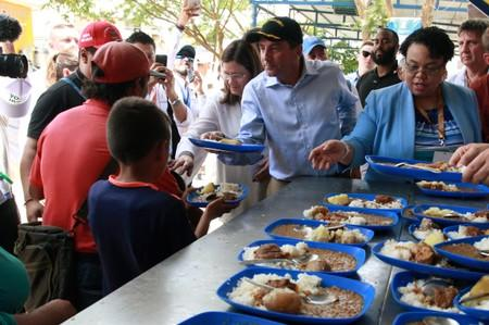 """U.S. Secretary of Health and Human Services Secretary Alex Azar distributes lunches, during a visit at the """"Divina Providencia""""migrant shelter in Cucuta"""
