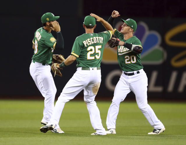 Oakland Athletics outfielders, from left, Chad Pinder, Stephen Piscotty and Mark Canha celebrate the team's 3-1 win over the Cleveland Indians in a baseball game Friday, June 29, 2018, in Oakland, Calif. (AP Photo/Ben Margot)