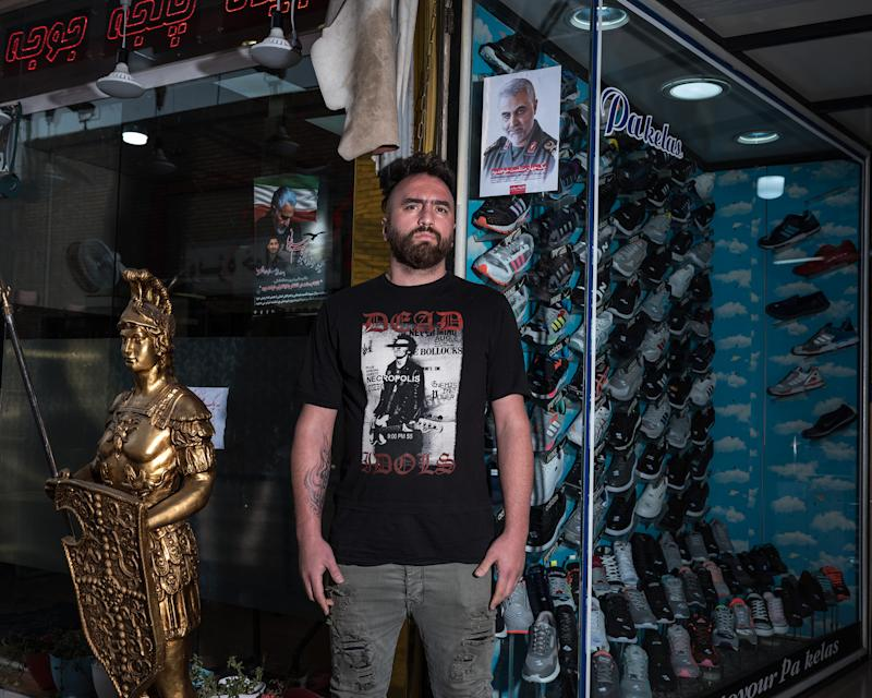 Ali, 29, sells shoes near the shrine to Shah Abdol Azim in Tehran. He hung a poster of Soleimani