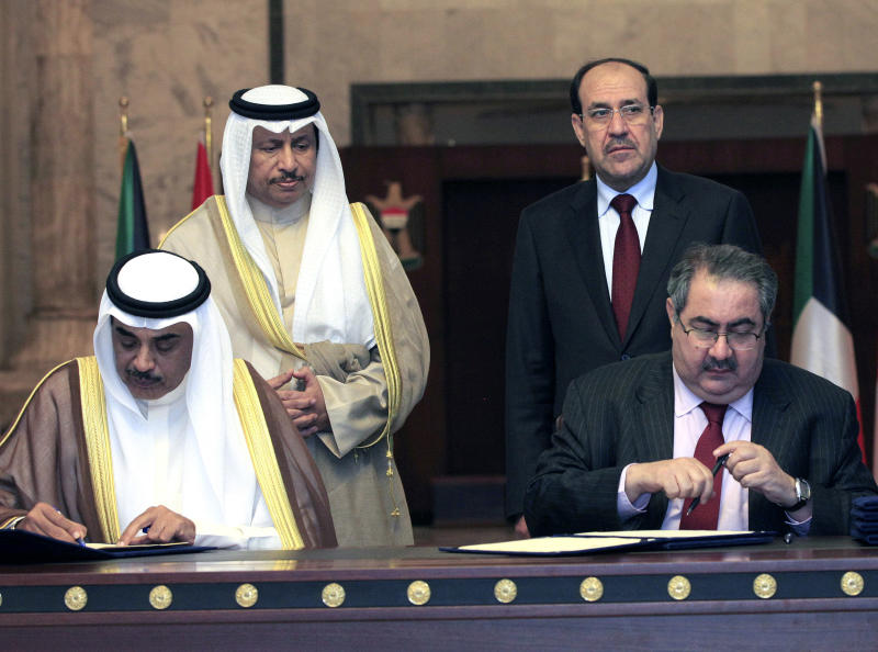 Iraqi Prime Minister Nouri al-Maliki, background right, and his Kuwait counterpart Sheikh Jaber Al Mubarak Al Hamad Al Sabah, background left, Iraqi Foreign Minister Hoshyar Zebari, foreground right, and Kuwaiti Foreign Minister Sheik Sabah Khalid Al Hamad Al Sabah, foreground left, sign agreements in Baghdad, Iraq, Wednesday, June 12, 2013. Kuwait's prime minister has arrived in Baghdad on an official visit, signaling the improving ties between the two neighbors. Officials later signed a series of agreements aimed at improving bilateral ties in the economic, transportation and other sectors. (AP Photo/ Karim Kadim, Pool)