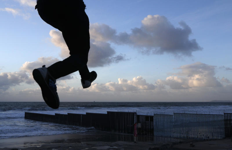 Resident Victor Jimenez practices his parkour skills on the beach near the U.S. border fence, in Tijuana, Mexico, on Friday, Nov. 30, 2018. Mexican authorities began moving Central American migrants out of an overcrowded shelter near the U.S. border and taking them to a former concert venue much farther away in Tijuana. (AP Photo/Rebecca Blackwell)