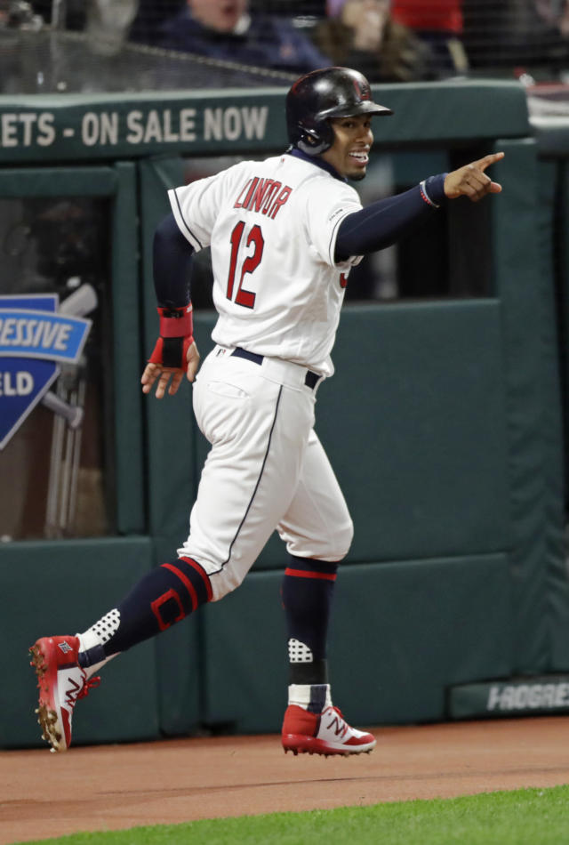 Cleveland Indians' Francisco Lindor looks over at Jose Ramirez at first base after Lindor scored on a two-run single by Ramirez in the second inning during the second game of a baseball doubleheader against the Atlanta Braves, Saturday, April 20, 2019, in Cleveland. (AP Photo/Tony Dejak)