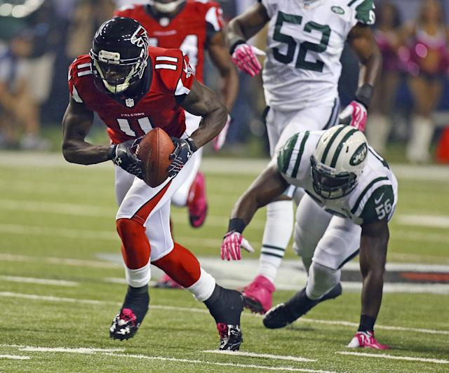 Atlanta Falcons wide receiver Julio Jones scoops up a fumble by teammate Roddy White in front of New York Jets linebacker Demario Davis during the first half of an NFL football game Monday, Oct. 7, 2013, in Atlanta. (AP Photo/Atlanta Journal Constitution, Curtis Compton)