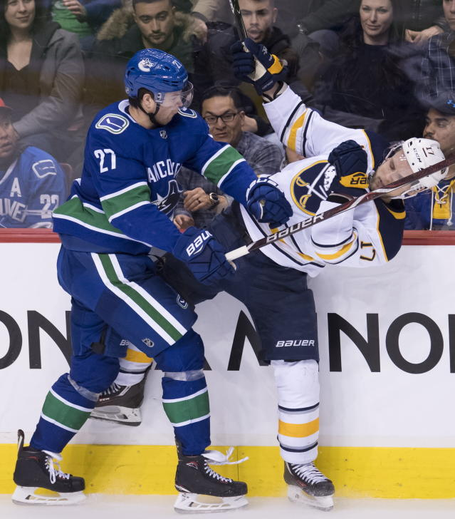 Vancouver Canucks defenseman Ben Hutton (27) goes into the boars with Buffalo Sabres center Vladimir Sobotka (17) during the second period of an NHL hockey game Friday, Jan. 18, 2019, in Vancouver, British Columbia. (Jonathan Hayward /The Canadian Press via AP)