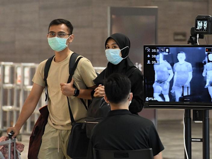 <br>A couple walk past a temperature screening check at Changi International Airport in Singapore on February 27, 2020.
