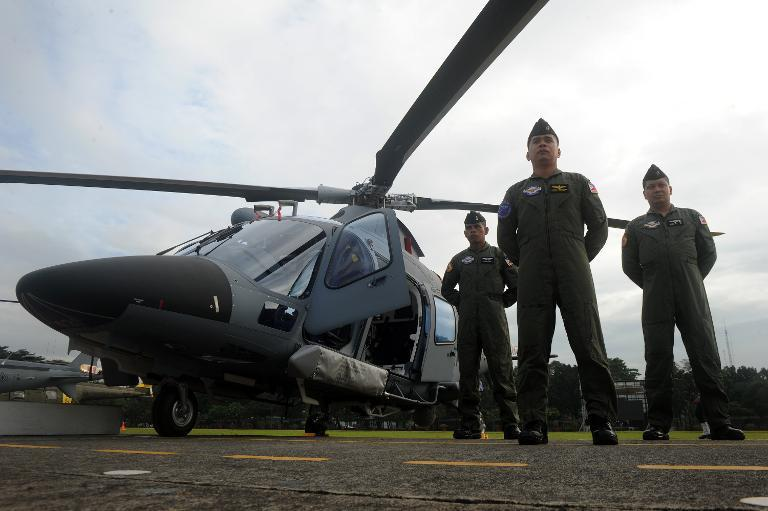 Philippine Navy personnel stand in formation beside Augusta Westland 109 Power Helicopters at the Armed Forces of the Philippines headquarters in Manila on December 19, 2013