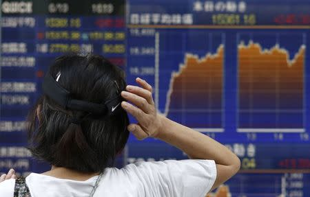 A woman scratching her head looks at an electronic board showing the graph of the recent fluctuations of Japan's Nikkei average outside a brokerage in Tokyo