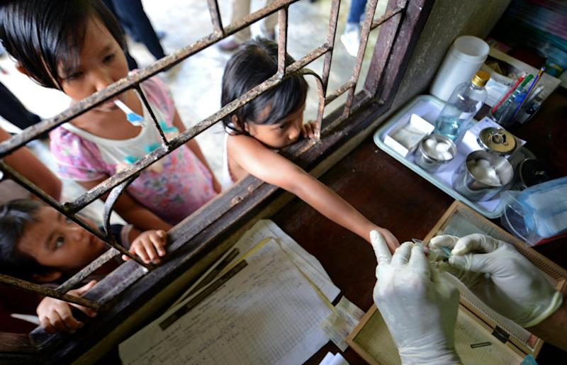 A Thai health official performs a blood test on children at a Malaria clinic in Kanchanaburi province near the Thai-Myanmar border on October 26, 2012